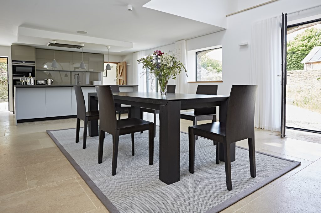 Fibre WOOL CLASSIC FLATWEAVE LUNAR rug with Ash linen binding under dining table